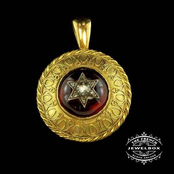 Etruscan Revival Garnet Pendant  This luscious cabochon garnet is set within a round Etruscan revival 15ct yellow gold and pendant, the central silver star is set with a pearl and diamonds, circa 1870.