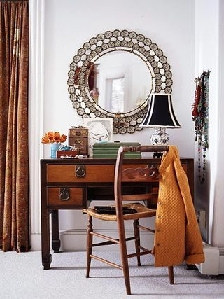 Dark wood dressing table with round mirror.