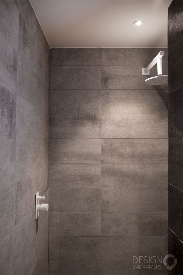 Maatwerk Moderne badkamers met overall grijze look, met mat witte kranen en mat witte douche set. Solid Surface (Corian) wastafel, spiegel met LED verlichting die in kleur en sterkte aan eigen smaak aan te passen is | #design_badkamers_breda #breda_design_badkamers
