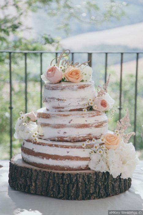 Naked cake con fiori freschi a piani per un matrimonio rustico