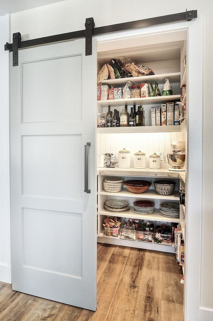 Modern pantry design with an elegant sliding barn door [Design: Dwellings Design Group]