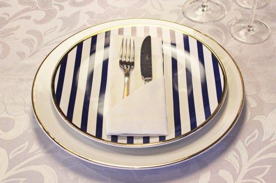 Também é possível utilizar o guardanapo para acomodar os talheres. Isso vai depender do número de pratos servidos e da quantidade de talheres utilizada. O prato raso é Coup Lusitana e o Sousplat possui filete em ouro.