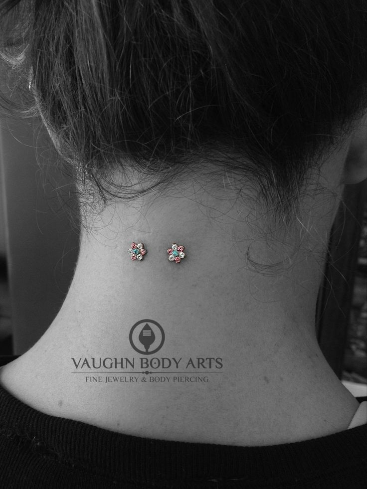 vaughnbodyarts:  This is Candace's nape piercing Cody did four years ago. She stopped by the studio to pick out some new threaded ends and chose these gorgeous flowers from Anatometal. Thank you, Candace!