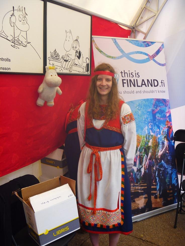 Una guapa finlandesa posa junto a un troll de peluche, figura folklórica de su país, en el stand de Finlandia de la Feria de Las CUlturas Amigas 2013