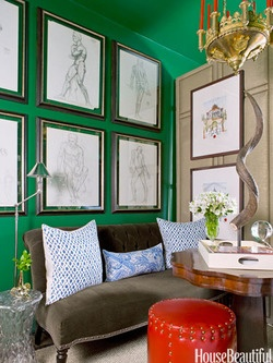 Emerald room with coral accent, large gold frames on gallery wall