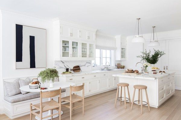 """Muller explains that they """"kept the palette very neutral so that the materials throughout the house could really be appreciated."""" That ethos is on full display in the home's kitchen, which is nearly all white from top to bottom. The only stray color comes by way of simple Hans Wegner stools and chairs and a dining bench covered in Victoria Hagan linen."""