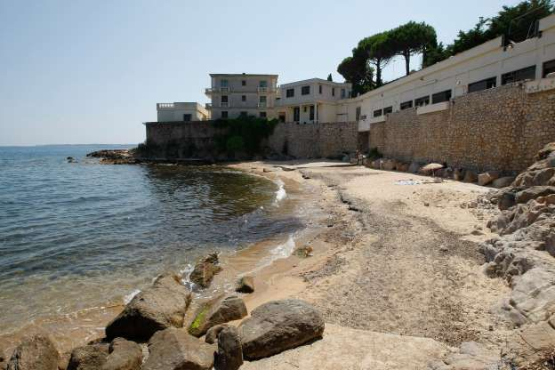 """In this photo dated Friday July 17, 2015 a view of the public beach called """"La Mirandole"""" located below a mansion owned by the Saudi royal family in Golfe Juan Vallauris, southern France. Last week, angry beachgoers won a temporary halt to unauthorized work ahead of the royal visit, notably a cement slab on the sand for an elevator allowing direct beach access from the mansion."""