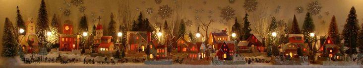 Antique Christmas cardboard house putz (village) on fireplace mantel at night (50K)