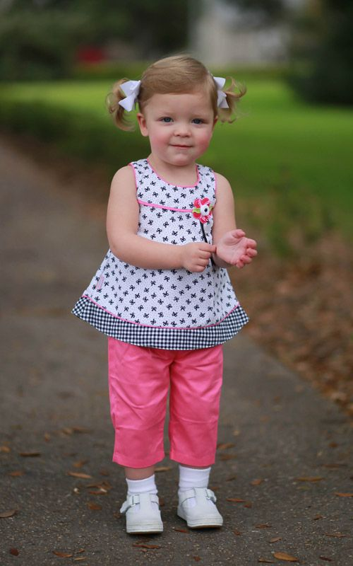 Our new 'Bubbly Black Bows Dress with Pink Pants' will look perfect on your little one! Can't you already see her playing in it? The sleeveless dress has a pink ribbon running across the chest. Laying
