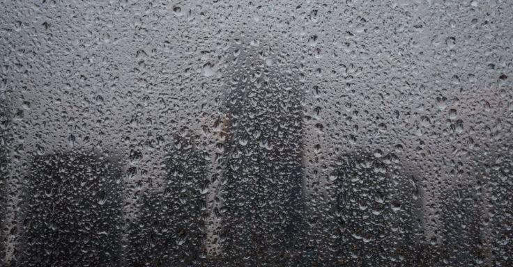 Silhuetas de arranha-céus são vistas atrás de uma janela coberta por pingos de chuva em Frankfurt, na Alemanha.  Fotografia: Frank Rumpenhorst/AFP.
