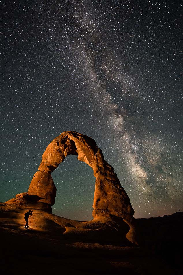 Self-portrait of the photographer, Travis Burke, shooting the Milky Way under Utah's Delicate Arch, with a little creative lighting from a flashlight.