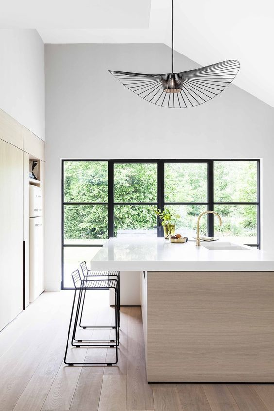 Minimalistic white kitchen in contrast with black assymetric lighting, chairs and framed windows.