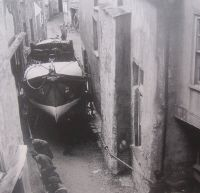 An old photograph of the lifeboat being pulled through the narrow streets of Port Isaac.