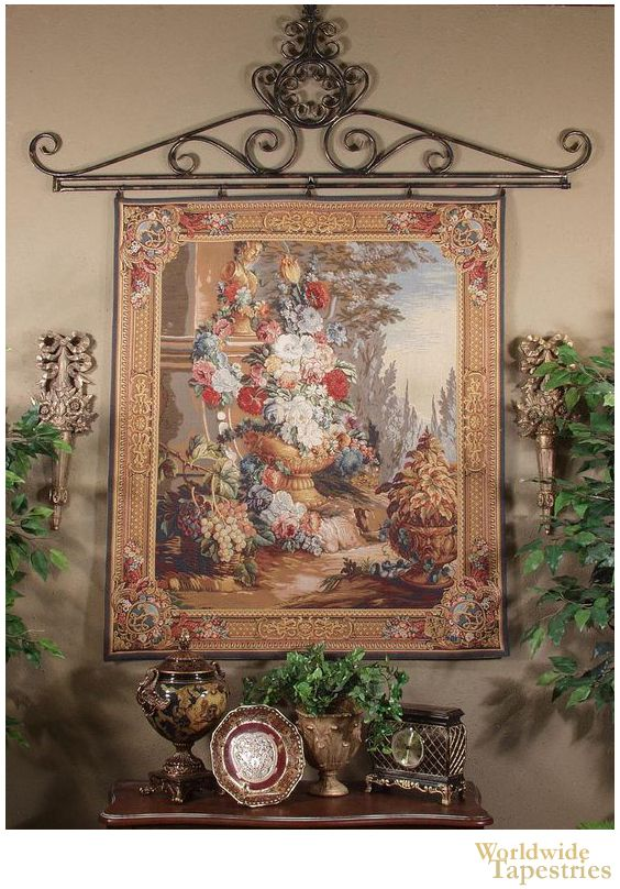 """This gorgeous """"Bouquet Alfresco"""" tapestry shows a large urn of flowers in the French countryside. This French tapestry shows a still life of flowers, with a large variety of blooms, set on a river bank, where potted plants, baskets of grapes and fruit, and a pillar with gold statuette decorates the scene."""