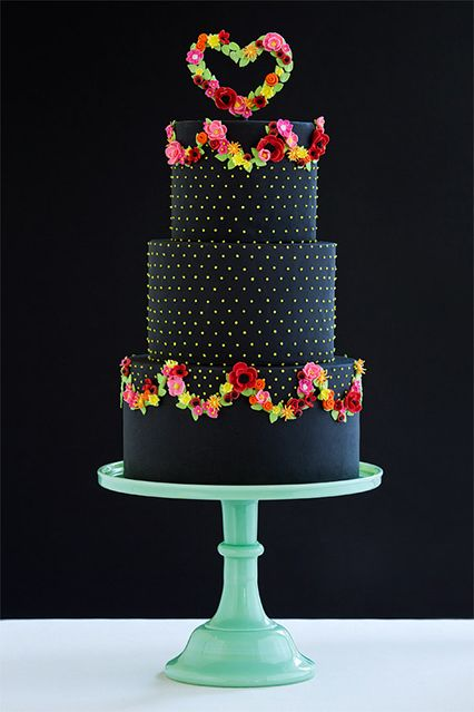 """""""The idea was to create a cake using traditional elements, but in unexpected colors,"""" says Erin Gardner of Wild Orchid Baking Company, in Dover, New Hampshire. """"Black cakes are often thought of as goth, but I wanted to make it pretty."""" Festooned with dots and garlands of flowers that reference goods from Rifle Paper Co., this one's utterly glamorous."""