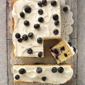 A sponge traybake full of blueberries topped with cream and blueberries scattered on top