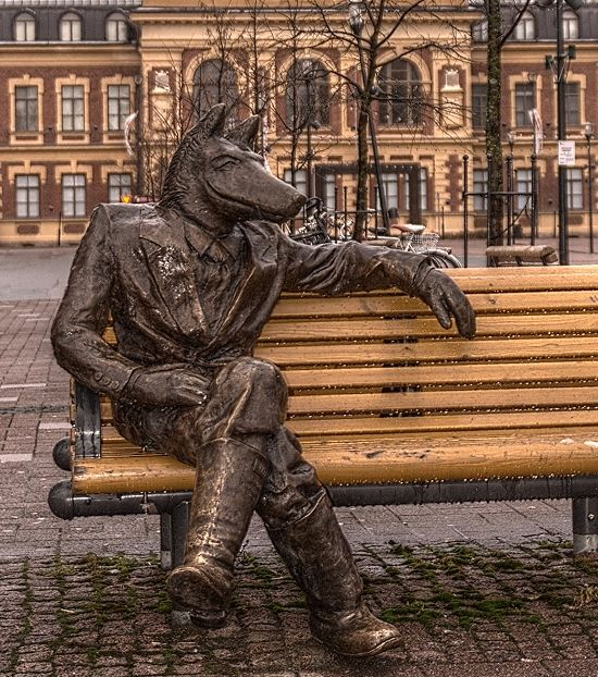 Wolf sitting in front of the City Art Museum of Joensuu, Finland