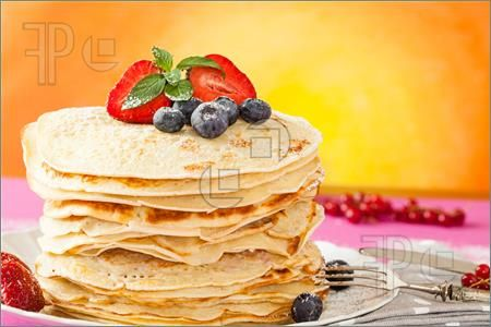 Image of Stack of pancakes ornated with red fruits, mint leaves and powdered sugar.