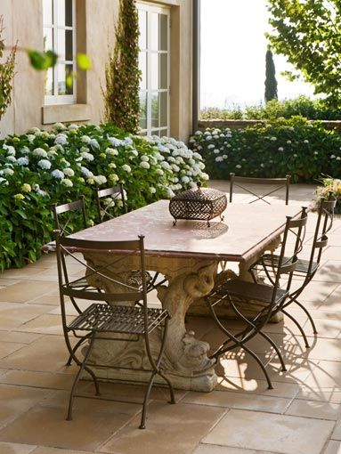 Beautiful stone table with metal chairs and hydrangeas in the beds