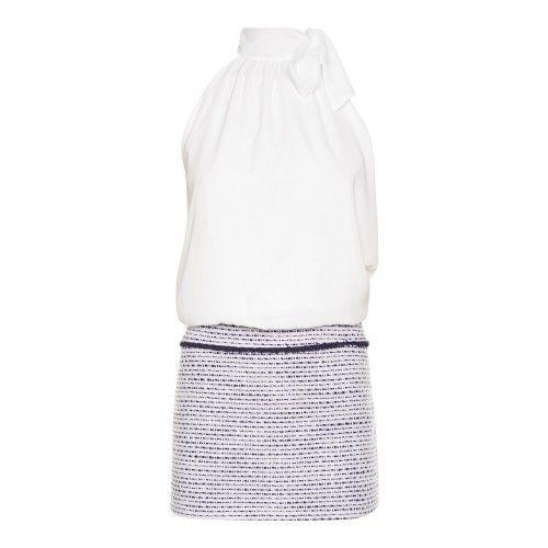 Tweedelige jurk zonder mouwen en loszittend ecru-kleurig haltertopje bovenaan. Strik aan de bovenzijde als detail. Tweedrokje onderaan waarin lurex verwerkt is. De ritssluiting bevindt zich aan de zijkant. De pop draagt een S.