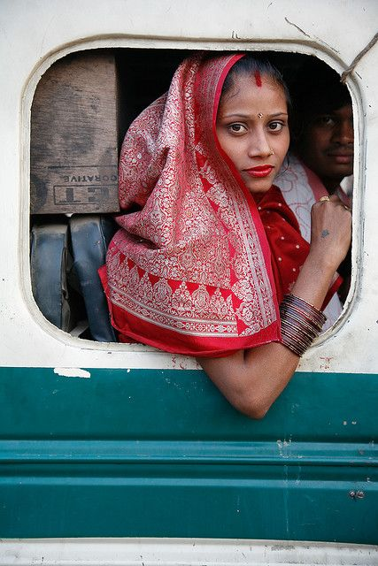 Woman on Bus    11 November 2007. Indian woman wearing a red sari looking out of a square bus window. Agra, Uttar Pradesh, India