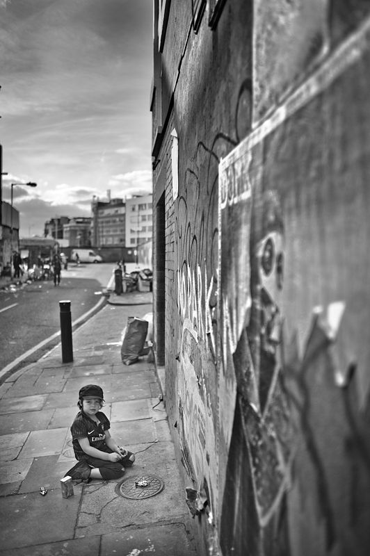 Kid playing on the pavement, Brick Lane, London.