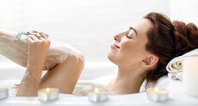 Femme se rasant les jambes dans la douche