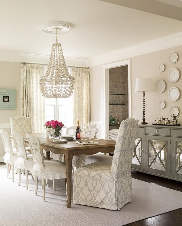 Beautiful dining room features a French dining table lined with white cane back dining chairs with skirted seat cushions as well as slipper captain dining chairs upholstered in Braemore Fioretto Sprout Fabric atop a gray rug illuminated by an Oly Studio Flower Drop Chandelier.