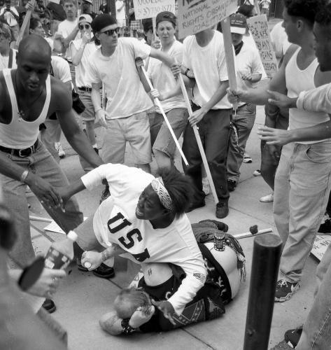 Keshia Thomas takes care of a Neonazi, that he will not be killed from a Lynch Mob, and showed out what it means to stand up for human rights. Es war der 22. Juni 1996 in Ann Arbor (Michigan). Eine Gruppe von Ku-Klux-Klan-Mitgliedern hielt in den Straßen der Stadt eine Kundgebung ab. Parallel versammelten sich rund 300 Gegendemonstranten. In dem Anti-KKK-Pulk: die 18-jährige Keshia Thomas, die durch das Foto berühmt werden sollte.