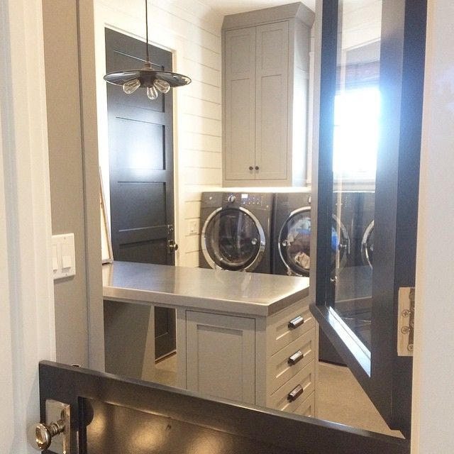 A glass barn door opens to a grey laundry room featuring dark grey washers and dryer placed below windows flanked by stacked grey shaker cabinets.