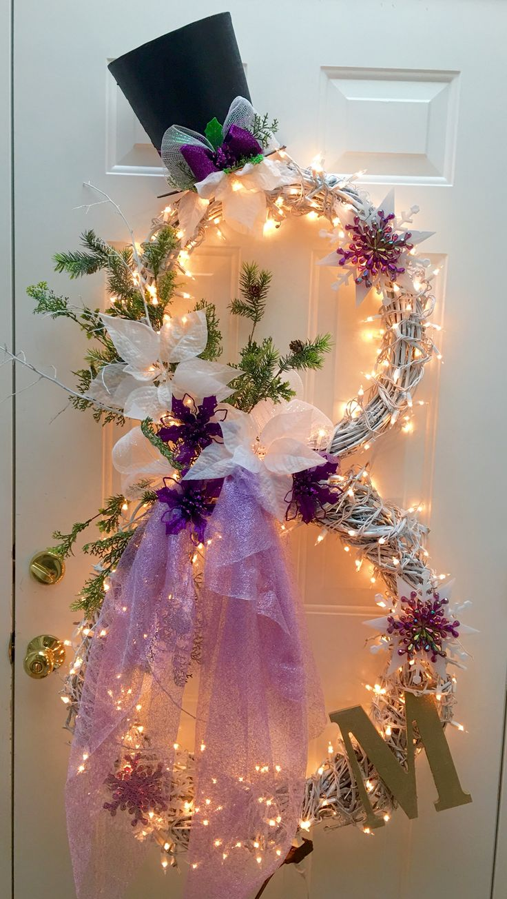 My 2015 Version of a winter snowman wreath in Purple:  I used two handmade grapevine wreaths wired together spray painted white, embellished with twigs painted white, purple iridescent snowflakes from the dollar store, and scrap fabric for scarf. Absolutely love it!  (The M is for my sister's last name)   (*** update December 2016): Everyone is asking about the hat. It came from AC Moore (end of the season sale 2014). It's a hard cardboard hat that I cut in half and decorated to match.