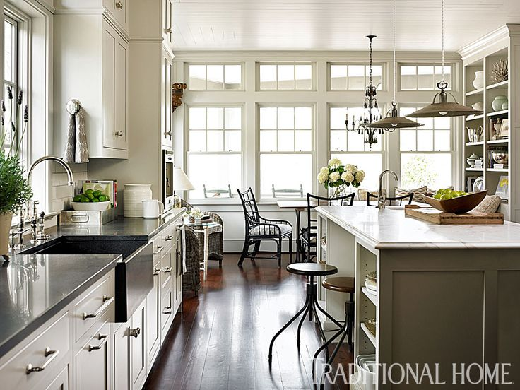 Breezy Lowcountry Home | Traditional Home -- A pair of rattan chairs by the windows and a breakfast nook with a cozy banquette offer guests comfortable places to enjoy a cocktail and talk to the host as he cooks. I love this kitchen