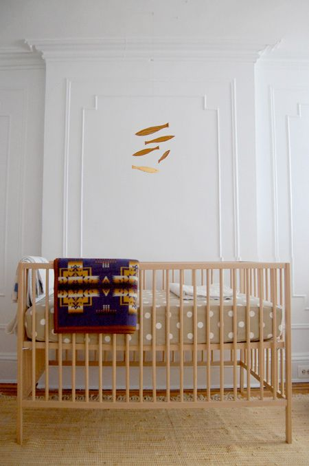 A great Scandinavian Modern look is easily achieved with an all-birch crib from IKEA and a natural wood Floating Fish mobile. Love that polka dot sheet in neutral beige too! And the juxtaposition of the modern crib against the traditional wall.