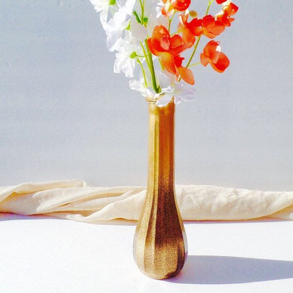 This handmade vintage vase was a clear glass vase that was painted with a 24kt gold paint, then sprayed along the bottom half with a brushed bronze paint to give it an aged look. It would look amazing displaying real or faux flowers on a mantle, kitchen table or even at a wedding. Its measurements are: 8.5 inches tall and 2.5 inches wide. Although this item is waterproof, I do not recommend submerging into water or putting it into the dishwasher. Spot cleaning only is best. Flowers in the…
