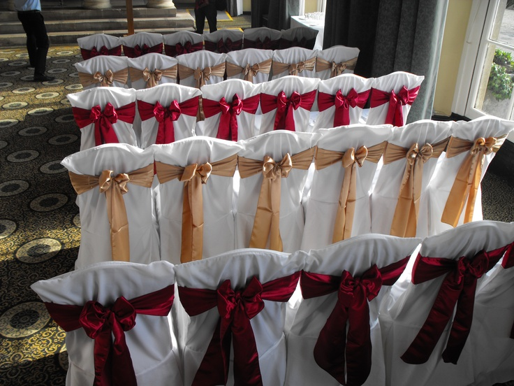 Alternating Gold and Claret Satin Bows on White Chair Covers