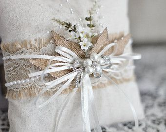 This adorable Ring Bearer pillow is perfect for your special day!  The pillow is made of ivory satin with the front of the pillow embellished with an ivory lace overlay. A touch of vintage romance, with an adorable finishing touch of a gift wrapped satin ribbon.  The pillow is approximately 9 inches square and is hand stuffed. The satin ribbon is 1½ inches wide with 1/8 streamers. The bow has a sweet organza flower with a rhinestone and pearl center as the focal point.
