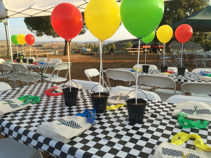 Centerpieces  I got black chalkboard pails from Hobby Lobby and filled with dirt and stuck balloons on sticks ... Representing a stoplight ... Ready ... Set ... Race!!! The favors were canvas bags filled with goodies and doubled for a piñata candy bag too! :)