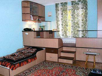 Комплект мебели для детской с рабочим местом на подиуме, выполняющим роль системы хранения.
