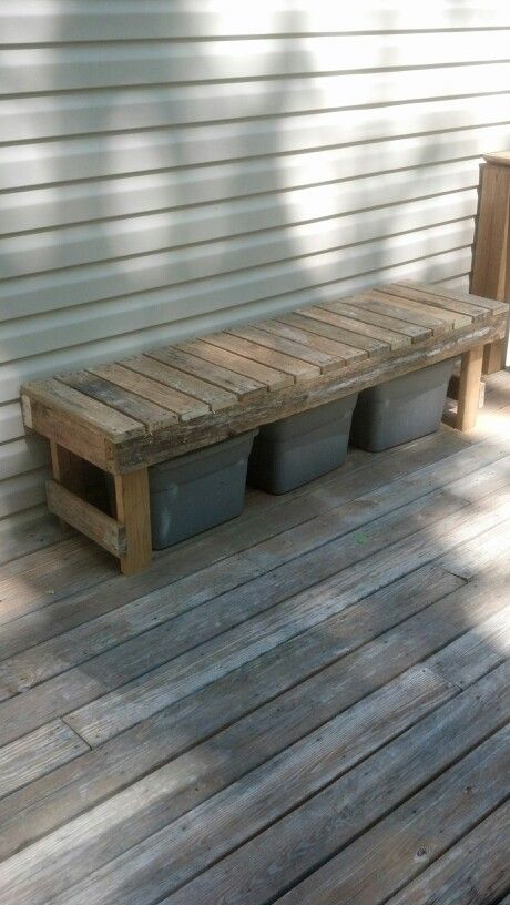 A bench made from pallets to hide the recycling bins.