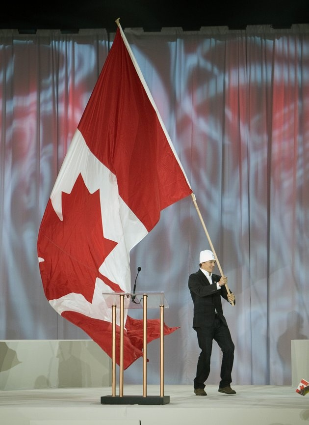 RICHMOND, CANADA - FEBRUARY 12: Simon Whitfield, Olympic gold and silver medalist in the triathlon, waves a Canadian flag during a ceremony for the one year countdown of the 2010 Olympic Games on February 12, 2009 at the Richmond Olympic Oval in Richmond, British Columbia, Canada.