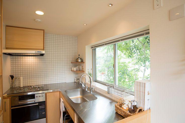 窓からグリーンが広がるキッチン。壁はタイル張りで掃除がしやすい。家を建てるにあたっては、プロトハウスにプロデュースを依頼。リオタデザインの関本竜太さんが設計した。