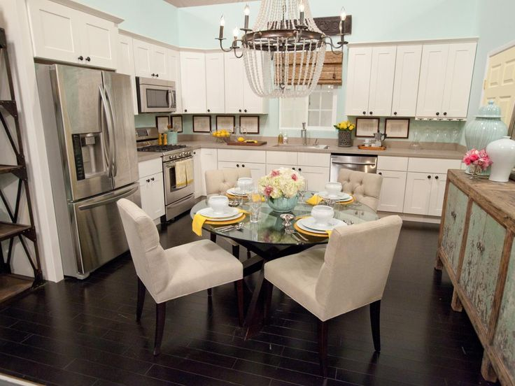 This blue and white kitchen and dining combo features white cabinets, stainless steel appliances, and a large crystal chandelier over the dining table. Light blue walls add a distressed buffet table add a colorful cottage feel to the space. While blue, white, yellow, and pink accessories and floral elements give the room a spring-like feel.