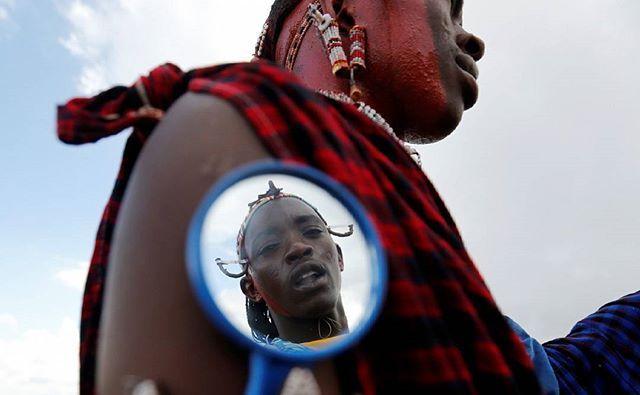 A Maasai moran athlete is reflected in a grooming mirror as he smears his colleague's face with red ocher paint during preparations for the 2016 Maasai Olympics at the Sidai Oleng Wildlife Sanctuary, at the base of Mt. Kilimanjaro, near the Kenya-Tanzania border in Kimana, Kajiado, Kenya December 10, 2016. REUTERS/Thomas Mukoya  #Maasai #MaasaiOlympics