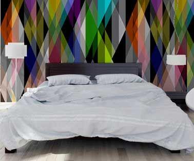 © Au Fil des Couleurs Audacieux, ce papier peint aux motifs géométriques multicolores posé en panneau décoratif pour former le support de tête de lit faite avec un panneau de bois peint en gris. les deux luminaires design et le linge de lit blanc tempèrent la fougue de la tapisserie.