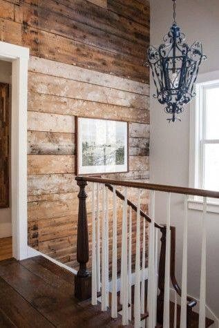 Rustic wood shiplap wall adds so much age and texture to this stairway with antique wrought iron chandelier