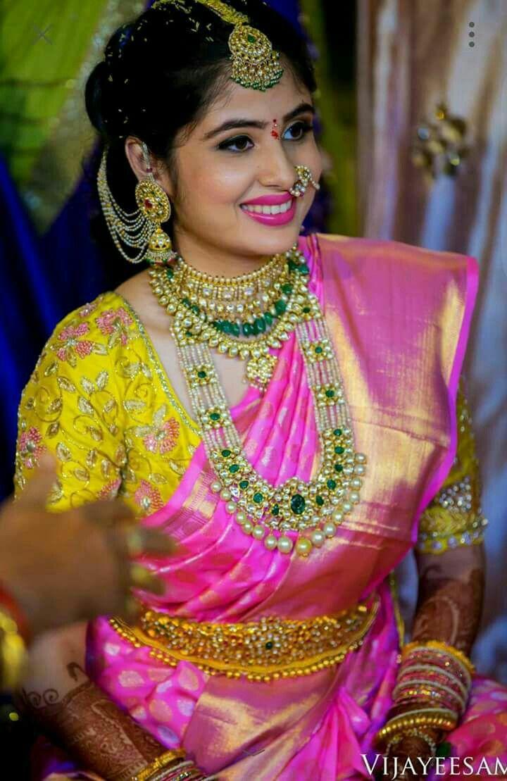 South Indian bride. Gold Indian bridal jewelry.Temple jewelry. Jhumkis.Pink silk kanchipuram sari with contrast pink blouse. Braid with fresh jasmine flowers. Tamil bride. Telugu bride. Kannada bride. Hindu bride. Malayalee bride.Kerala bride.South Indian wedding.
