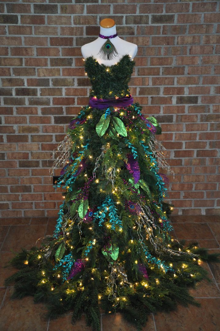 Christmas Tree Dress - Peacock inspired Christmas Tree gown on a mannequin. 600 lights and 6 feet tall! Made by A Ribbon Runs Through It. 2015www.aribbonrunsthroughit.com #chrismtastreedress