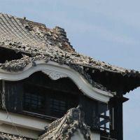 地震で崩落した熊本城の石垣。奥は天守閣(熊本市内)