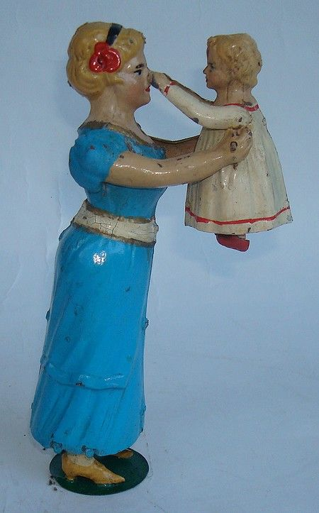 Unusual tin toy...looks like she's pinching her mother's nose!