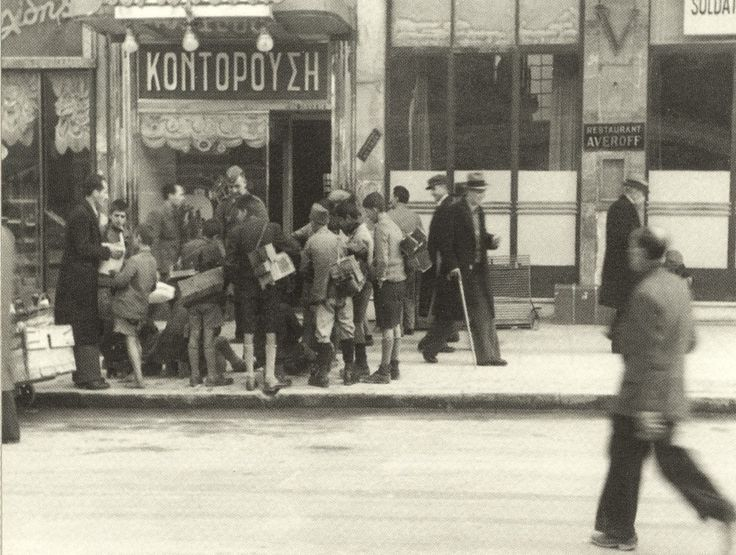 "Athens, Greece, winter of 1941-1942. Kids surround German officers asking for food outside ""Averof"" restaurant on Stadiou str."